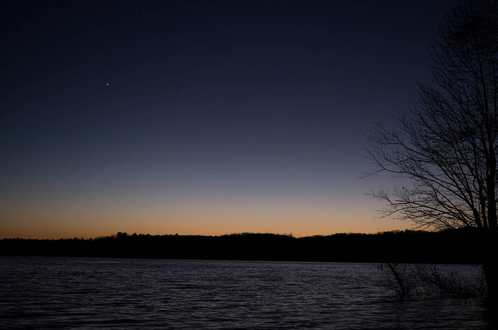 "Jupiter, left, and Saturn, right, are seen after sunset above Jordan Lake during the ""great conjunction"" where the two planets appear a tenth of a degree apart from one another, Monday, Dec. 21, 2020, near Chapel Hill, North Carolina. Credit: (NASA/Bill Ingalls)"